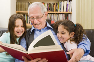 Grandfather reading to girls